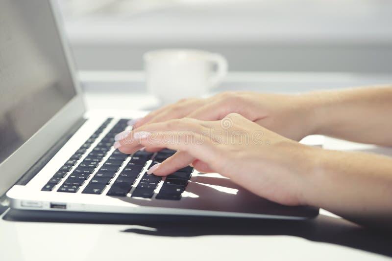 Kobieta pisać na maszynie na laptopie przy miejsce pracy kobietą pracuje w ministerstwo spraw wewnętrznych ręki klawiaturze obraz royalty free