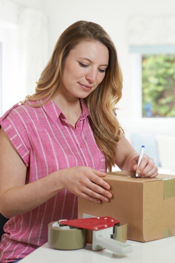 Kobieta Pisze adresie Na pakunku W Domu zdjęcie royalty free