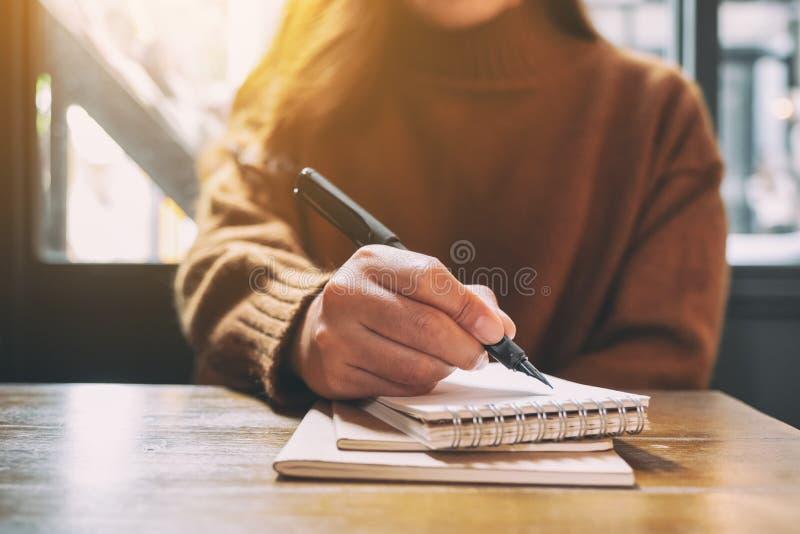Kobieta pisze na pustym notatniku z fontanny piórem na drewnianym stole fotografia royalty free