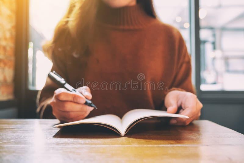 Kobieta pisze na pustym notatniku z fontanny piórem na drewnianym stole obraz stock