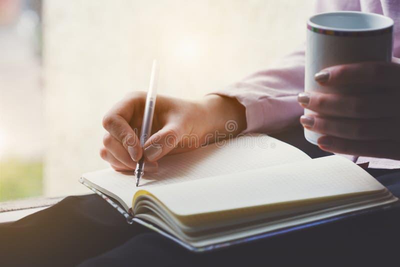 Kobieta pisze notatkach na notatniku z piórem i pije kawę zdjęcia stock