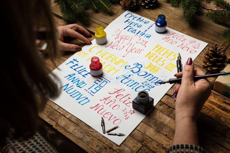 Kobieta pisze szczęśliwego nowego roku w różnych językach fotografia stock