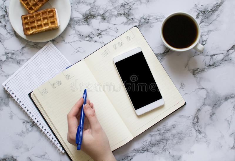 Kobieta planuje dzień, kawa, gofry, marmurowy tło, smartphone zdjęcia stock