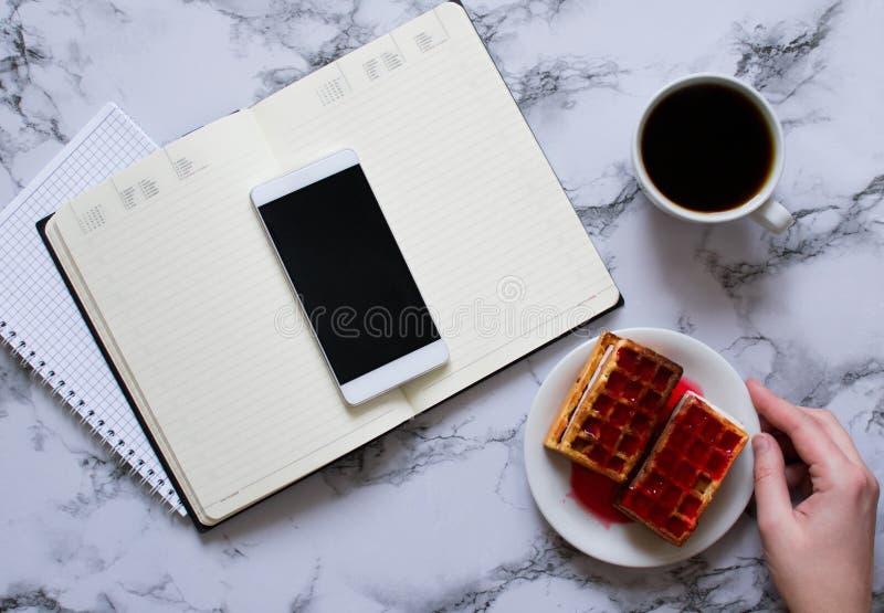 Kobieta planuje dzie?, kawa, gofry, marmurowy t?o, smartphone zdjęcie royalty free