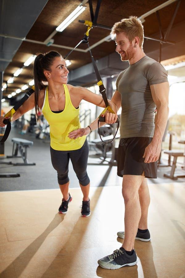 Kobieta pociąg w gym z trenera pomagać obraz royalty free