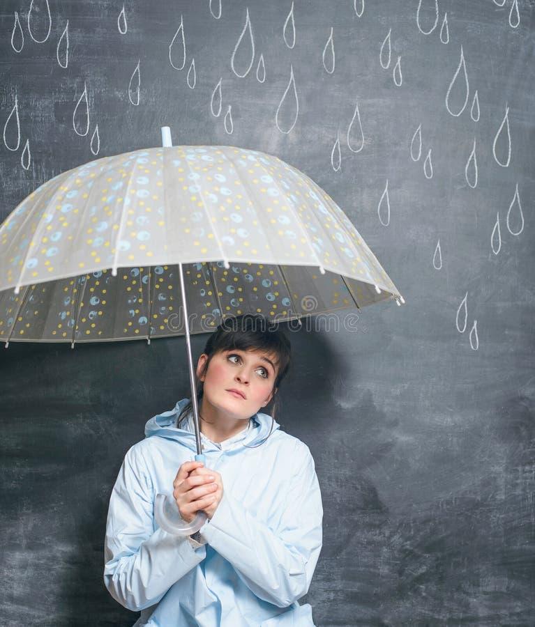 Kobieta pod parasolem na patroszonym kredowymi kroplami podeszczowy tło obraz stock