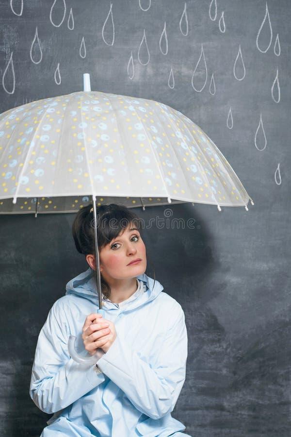 Kobieta pod parasolem na patroszonym kredowymi kroplami podeszczowy tło zdjęcie royalty free