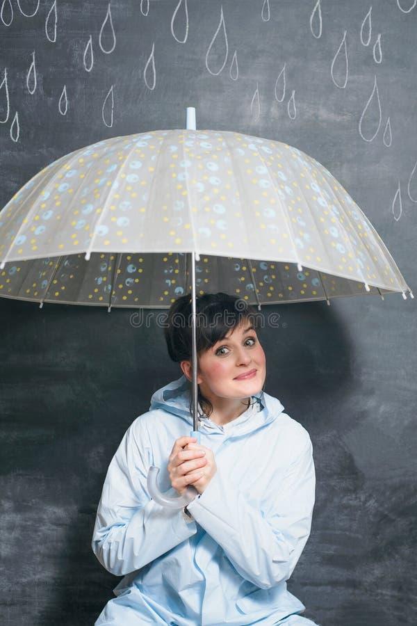 Kobieta pod parasolem na patroszonym kredowymi kroplami podeszczowy tło fotografia stock