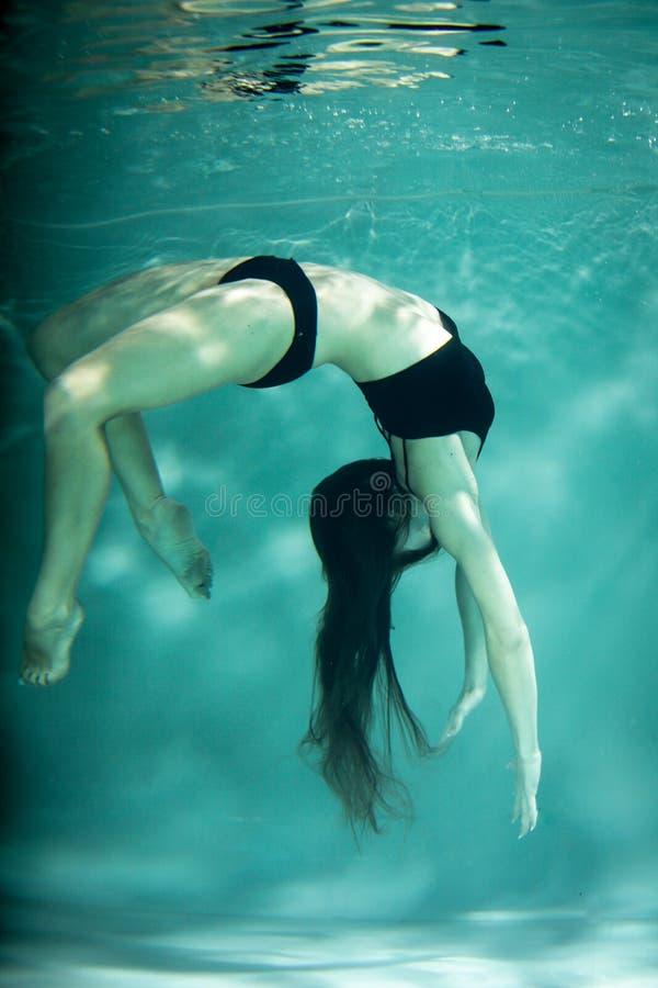 Kobieta pod wodą w czarni ubrania obraz royalty free