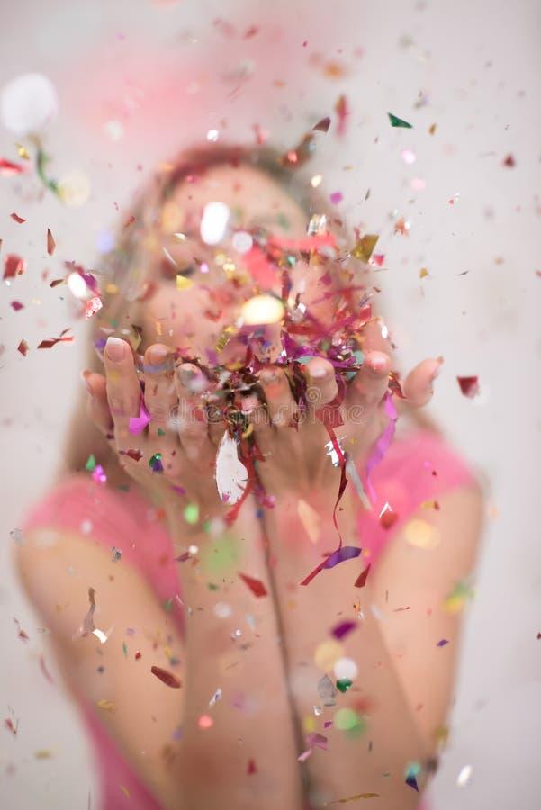 Kobieta podmuchowi confetti w powietrzu obraz stock