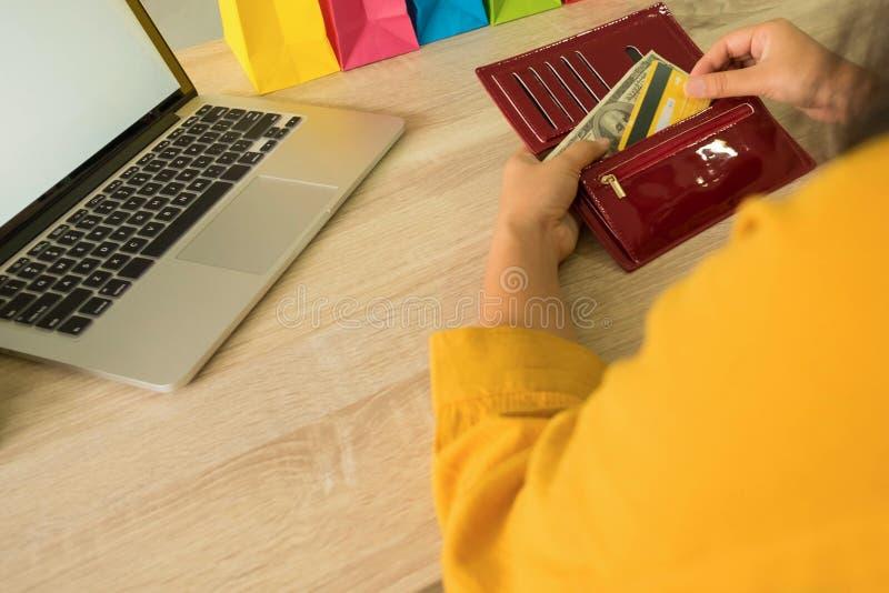 Kobieta podnosi kredytową kartę w portflu dla robić zakupy online obraz stock