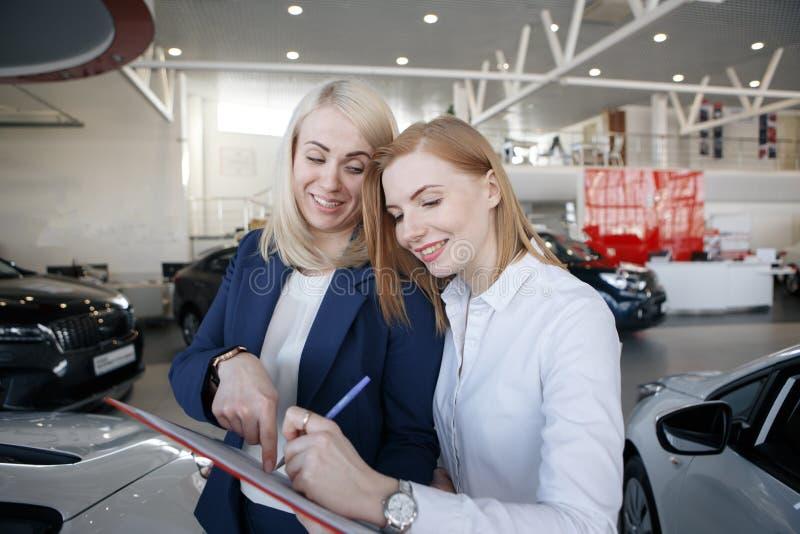 Kobieta podpisuje ubezpieczenie samochodu polisę agent wskazuje przy dokumentem fotografia stock