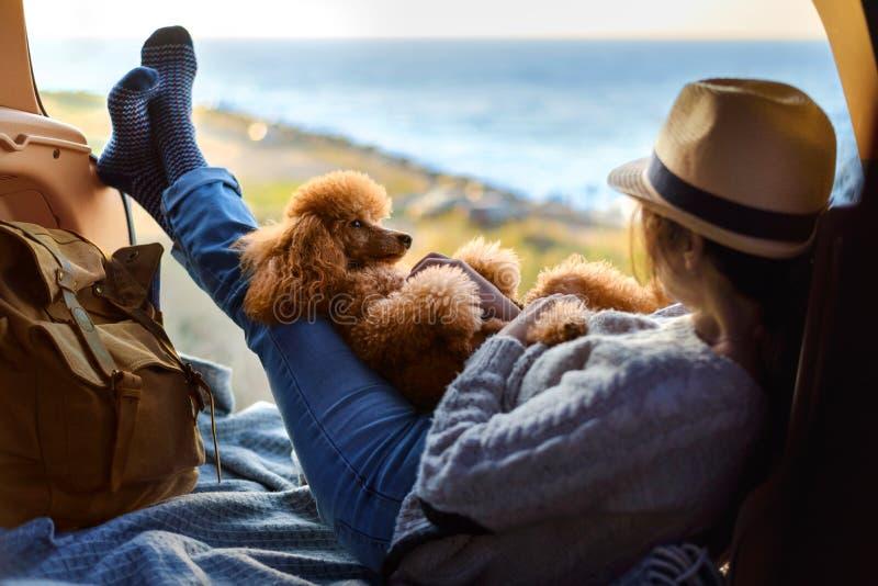 Kobieta podróżnik z psim obsiadaniem w samochodowym bagażniku blisko morza, dopatrywanie zmierzch obrazy royalty free