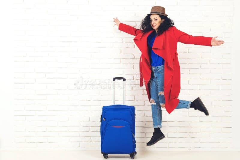 Kobieta podróżnik z walizką na białym ceglanym tle Szczęśliwa dziewczyna gotowa dla wycieczki Podr??owa? i styl ?ycia poj?cie mod zdjęcia royalty free