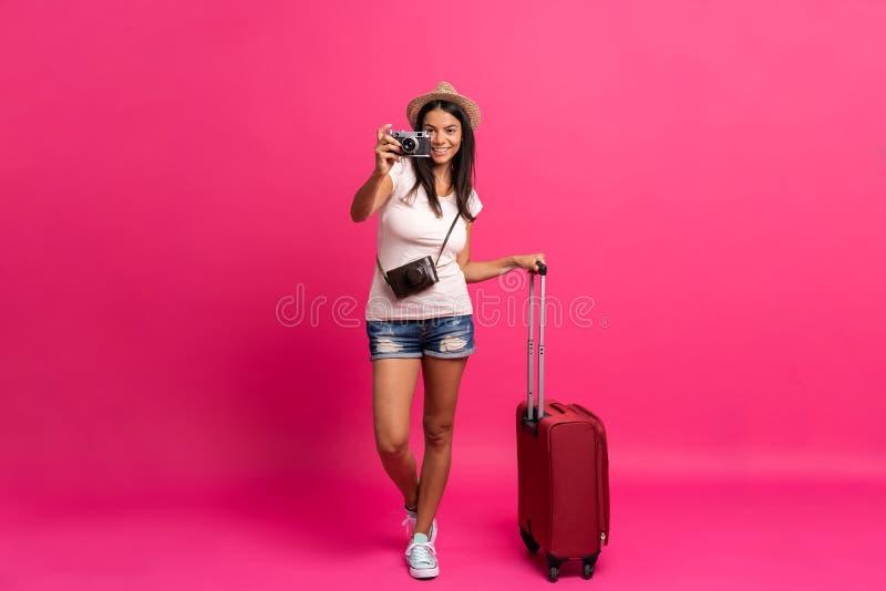 Kobieta podróżnik z walizką na koloru tle fotografia stock