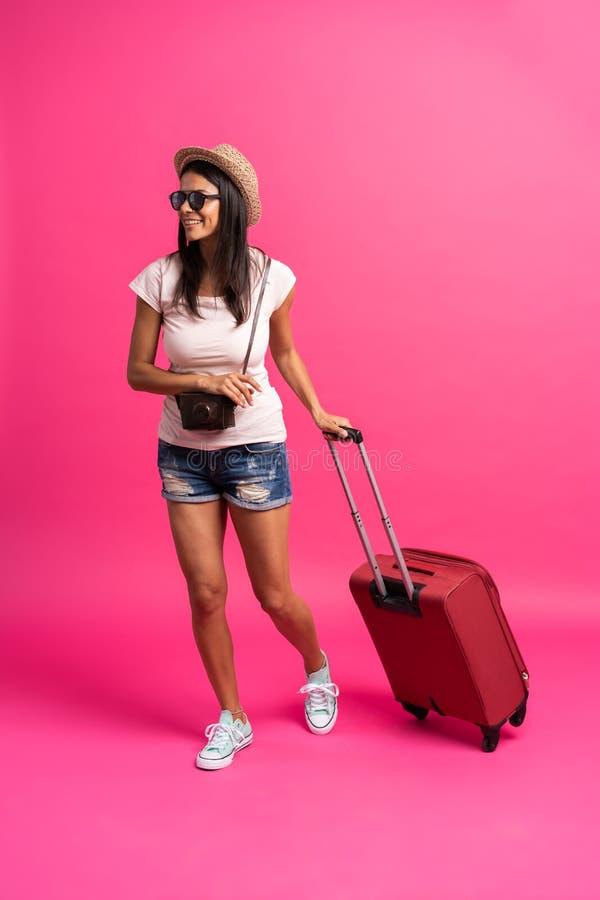 Kobieta podróżnik z walizką na koloru tle fotografia royalty free
