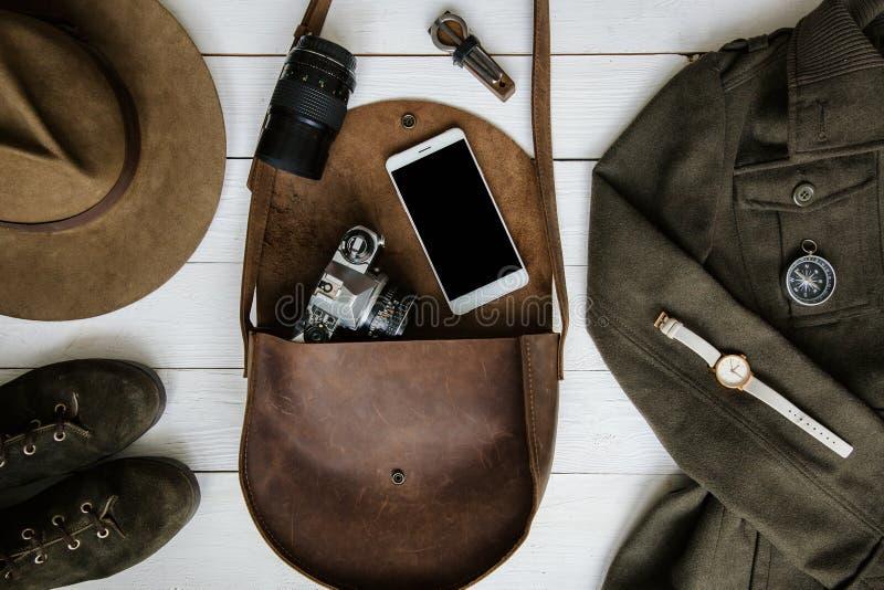 Kobieta podróżnika akcesoria na białym drewnianym tła mieszkaniu nieatutowym i odzież Brown rzemienna kiesa, wycieczkuje buty, ja zdjęcie stock