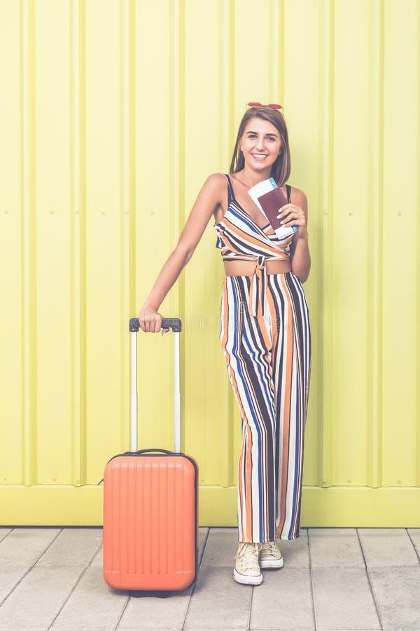 Kobieta podróżnika mienia walizka, paszport i bilety przeciw żółtemu tłu, obraz royalty free