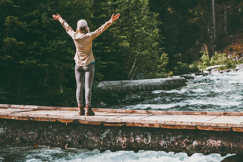 Kobieta podróżnika szczęśliwe nastroszone ręki na moscie nad rzeczną przygodą Podróżują zdjęcia royalty free