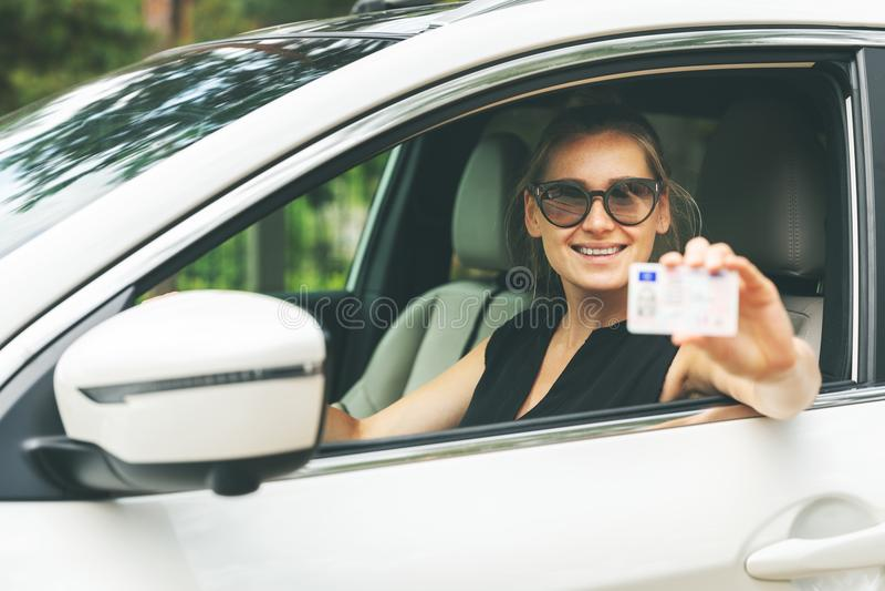 Kobieta pokazuje jej prawo jazdy przez samochodowej wygrany obrazy stock
