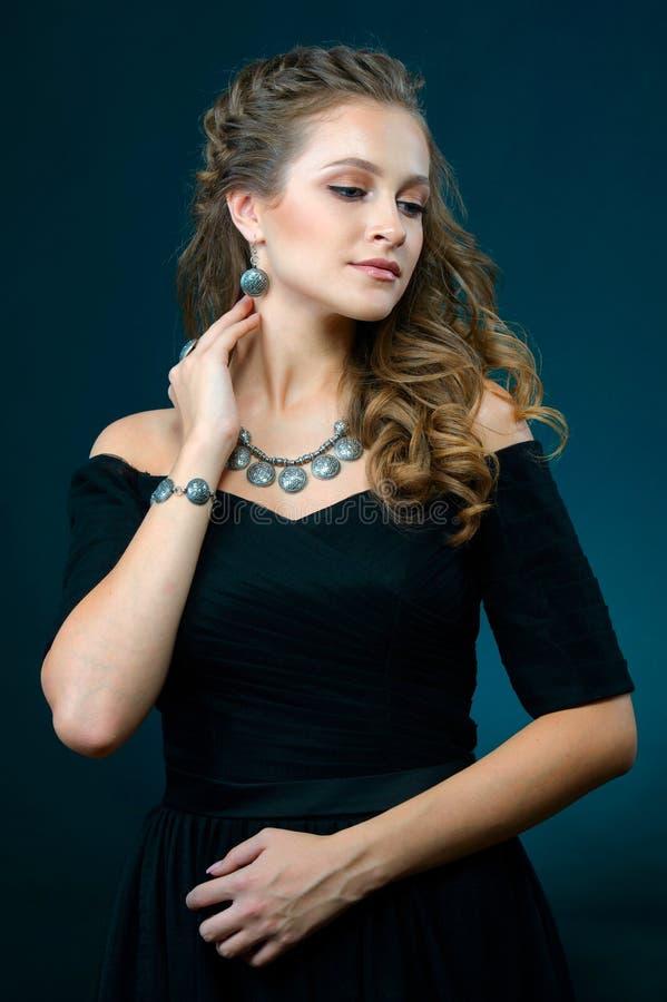 Kobieta pokazuje kolczyki kolia i pierścionek na błękitnym ciemnym backgroun fotografia stock