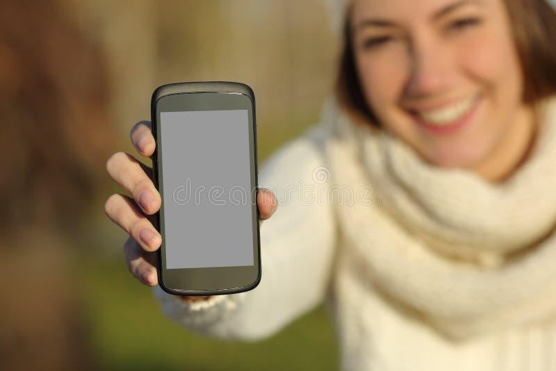 Kobieta pokazuje mądrze telefonu ekran w zimie outdoors obraz royalty free