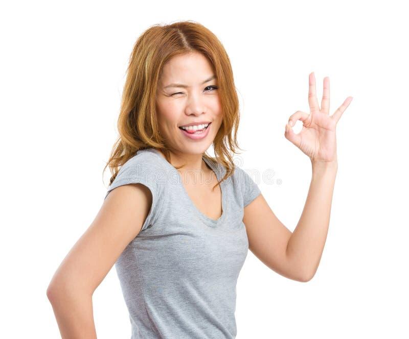 Kobieta pokazuje Ok znaka z mrugnięcia okiem fotografia royalty free