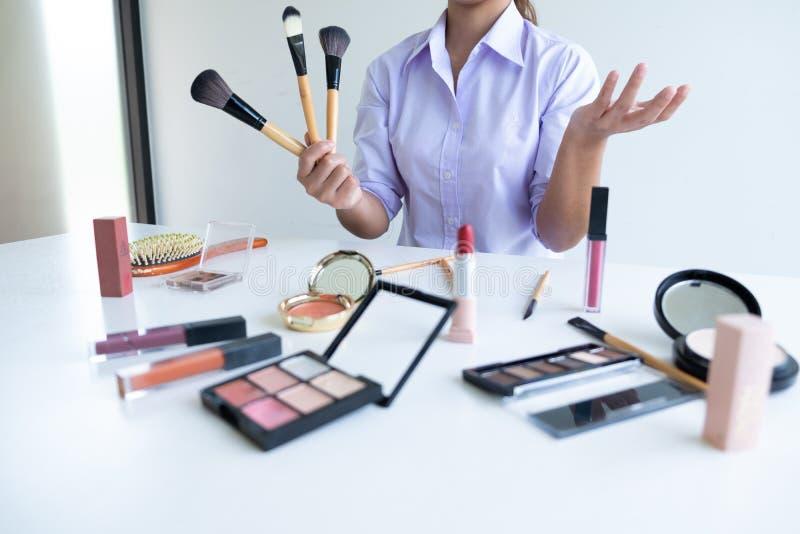 Kobieta pokazuje pięknu kosmetycznego produkt i transmisję ogólnospołeczna sieć internetem, piękna blogger online marketingowy po obraz stock