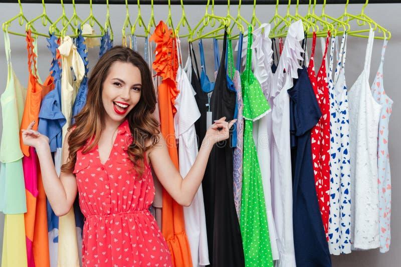 Kobieta pokazuje przy sukniami zdjęcie royalty free