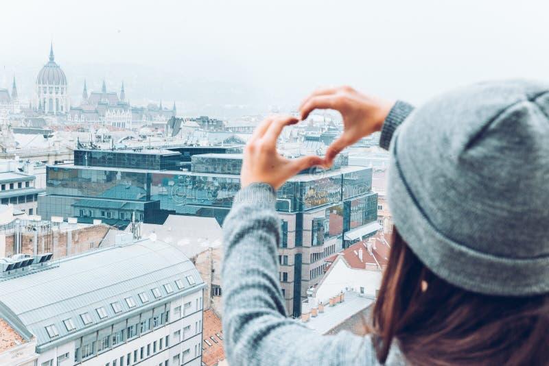 Kobieta pokazuje serce z rękami z pięknym widokiem stary europejski miasto na tle zdjęcie royalty free