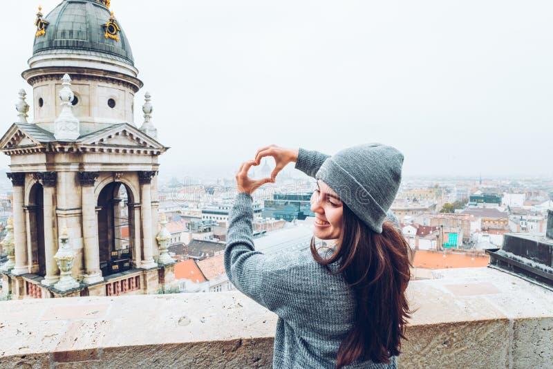 Kobieta pokazuje serce z rękami z pięknym widokiem stary europejski miasto na tle fotografia stock