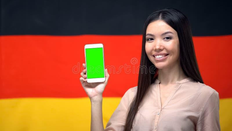 Kobieta pokazuje smartphone z zieleń ekranem, niemiec flaga na tle, app obrazy stock
