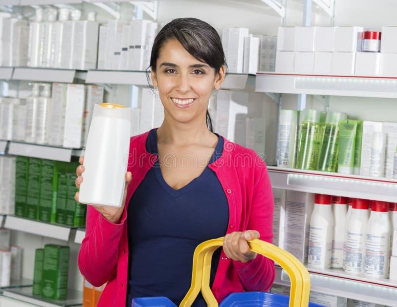 Kobieta Pokazuje szampon butelkę W aptece obraz royalty free