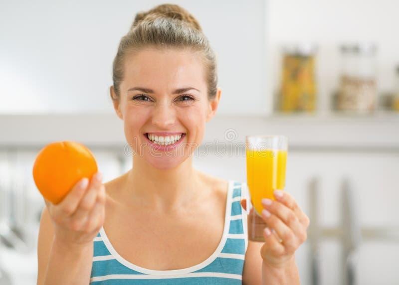 Kobieta pokazuje szkło sok pomarańczowy i pomarańcze fotografia royalty free