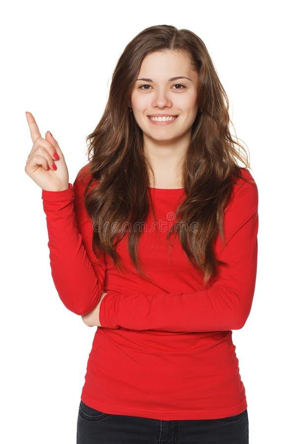 Kobieta pokazuje wskazywać i ono uśmiecha się zdjęcie stock