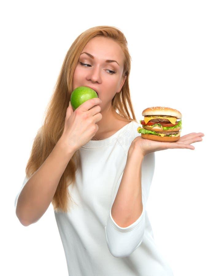 Kobieta porównuje hamburger kanapkę w ręce i zieleni jabłku obraz royalty free
