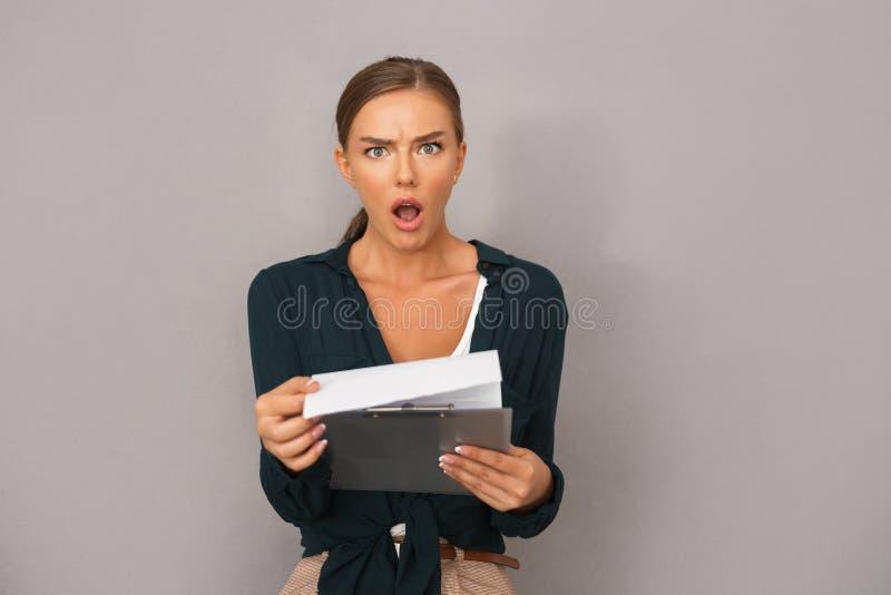 Kobieta pozuje nad popielatym ściennym tła mienia schowkiem z grafika zdjęcie stock