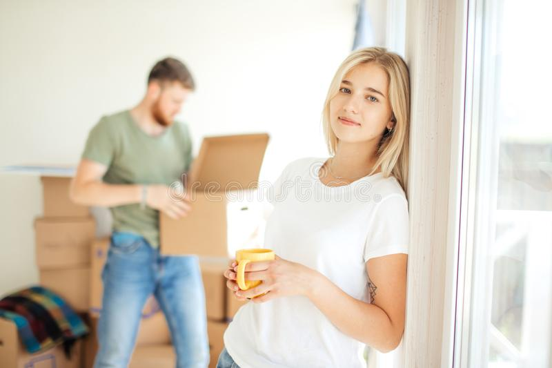 Kobieta pozuje przy kamerą podczas gdy jej mąż lub chłopak odpakowywamy pudełka pary ich domowy poruszający nowy zdjęcie stock
