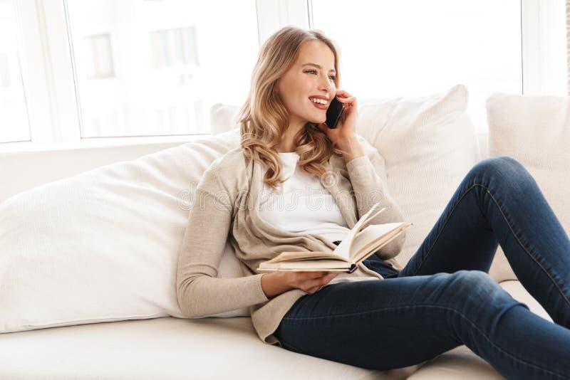 Kobieta pozuje siedz?cy indoors w domu opowiada? telefonem kom?rkowym zdjęcia stock