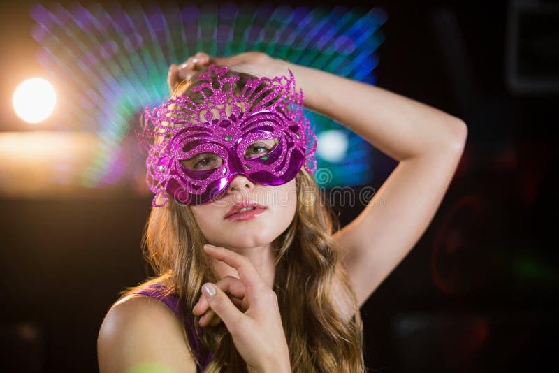 Kobieta pozuje z maskaradą w barze fotografia stock