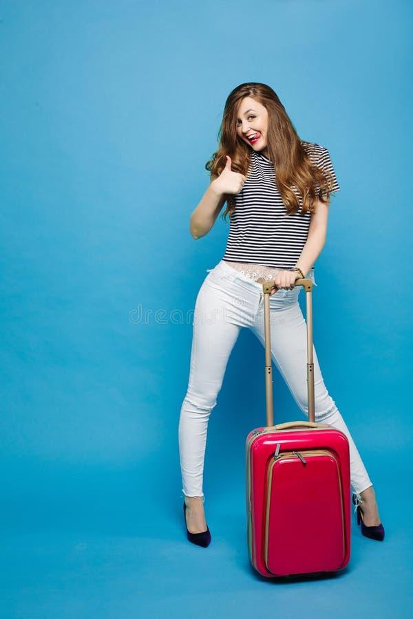 Kobieta pozuje z podróży torby pokazywać super i wtykać za fotografia stock