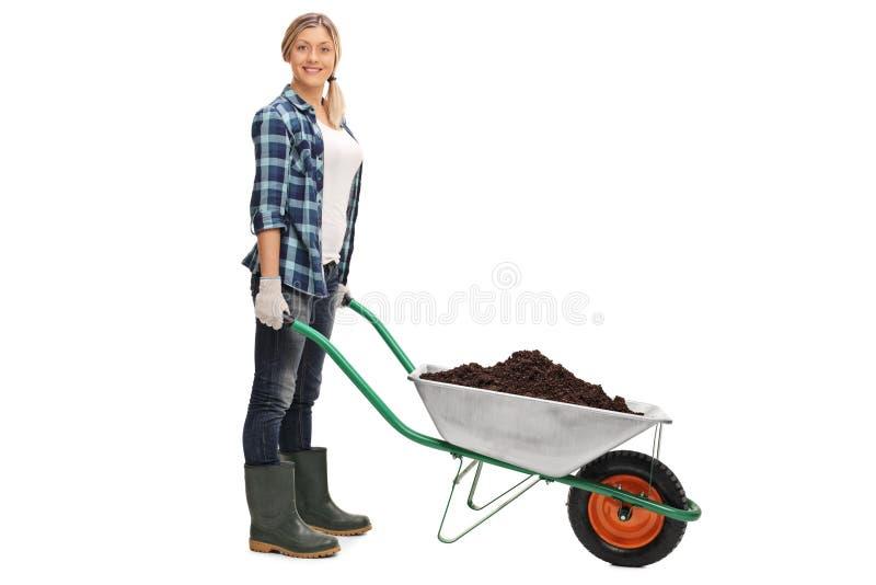 Kobieta pozuje z wheelbarrow brud pełno zdjęcie stock