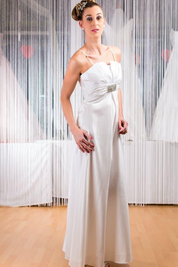 Kobieta próbuje ślubną suknię w sklepie obrazy stock