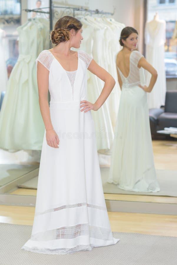 Kobieta próbuje na ślubnej sukni w bridal salonie obrazy royalty free