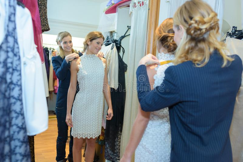 Kobieta próbuje na ślubnej sukni w sklepie z asystentem obrazy royalty free
