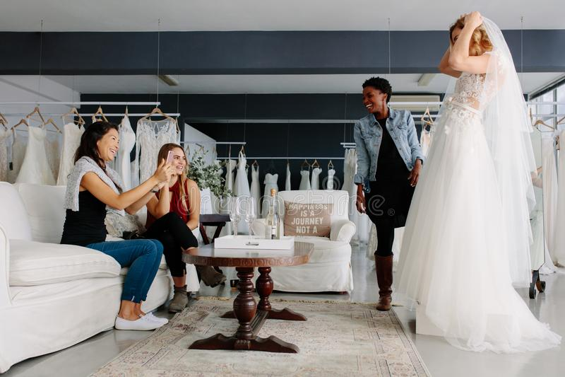 Kobieta próbuje na ślubnej sukni w sklepie z przyjaciółmi obrazy royalty free