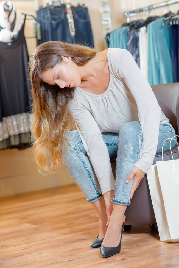 Kobieta próbuje na bucie w sklepie obrazy royalty free