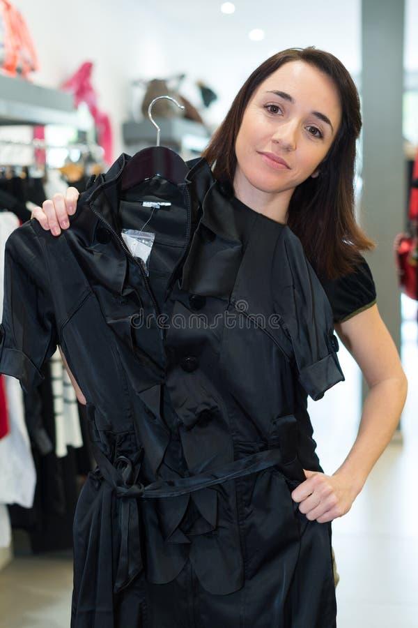 Kobieta próbuje na odziewa przy sklepem zdjęcie stock