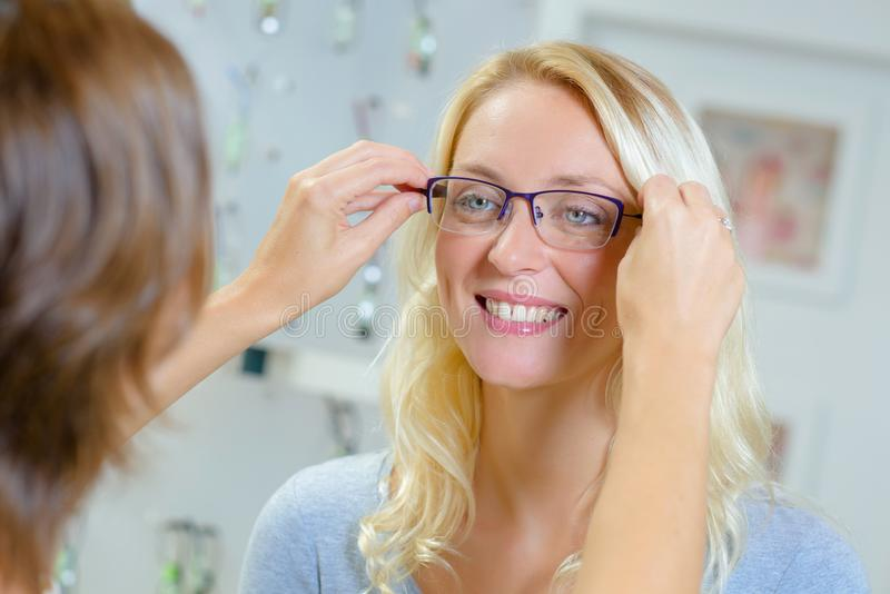 Kobieta próbuje na szkłach w okulistycznym sklepie zdjęcia royalty free