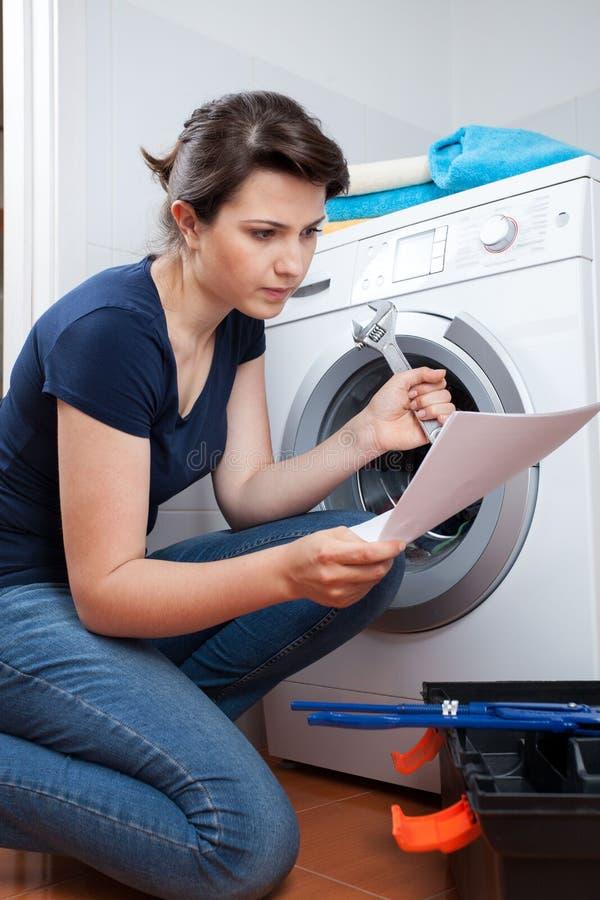 Kobieta próbuje naprawiać pralkę zdjęcia royalty free